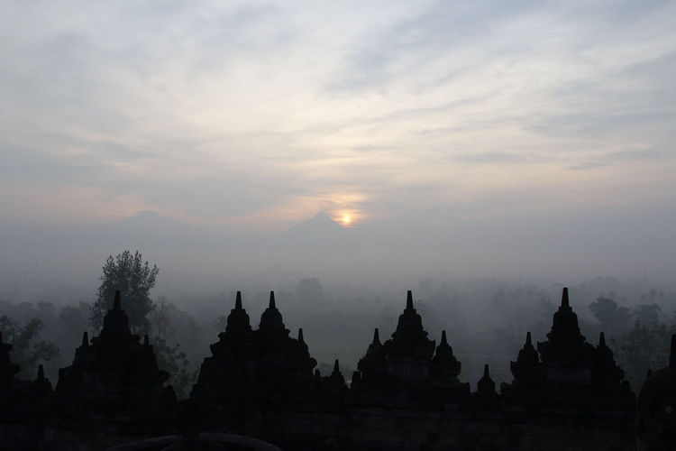 Silhouette Borobudur Temple with the mysteries forest surrounding during sunrise, Yogyakarta, Indonesia Ancient Borobudur Temple Java Yogyakarta Ancient Civilization Architecture Beauty In Nature Buddhism Built Structure Dawn Fog Forest History Mount Merapi Nature No People Place Of Worship Religion Religious Architecture Silhouette Sky Spirituality Sunrise Sunset Tree