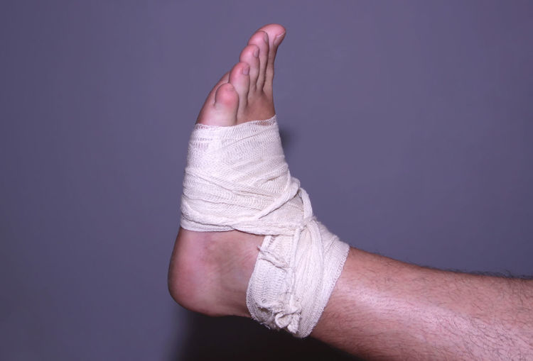 Low section of man with broken leg against gray background