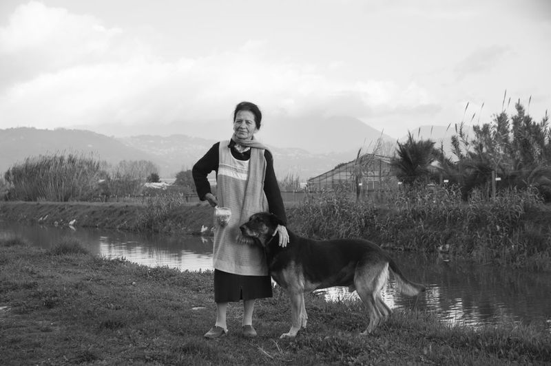 Full length of senior woman with dog standing by lake against sky