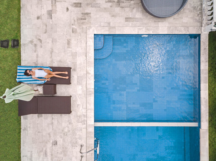 Man holding umbrella by swimming pool in city