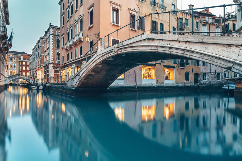 Reflection of arch bridge over canal in city