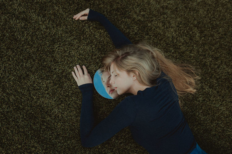 High Angle View Of Woman Lying Down On Field