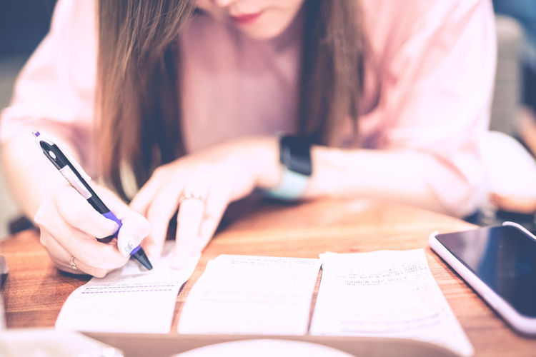 Midsection of woman writing in paper on table