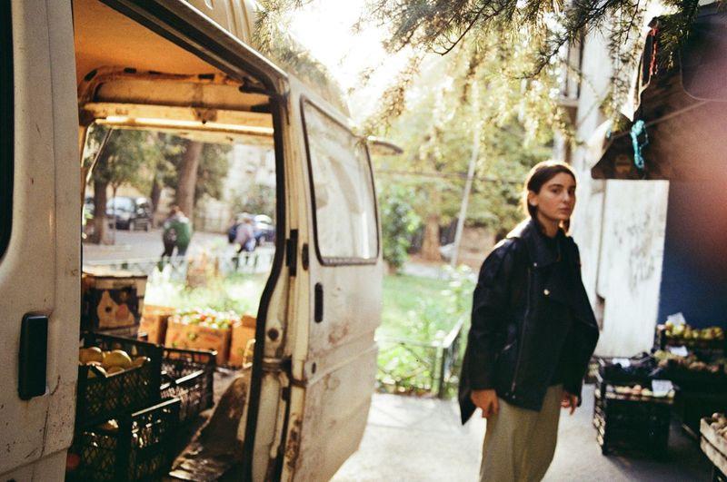 Portrait of woman standing by van outdoors