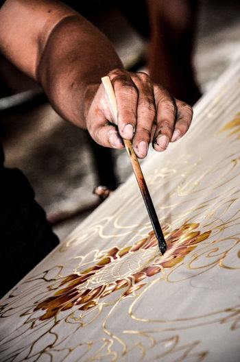 Cropped Image Of Man Painting Fabric In Factory