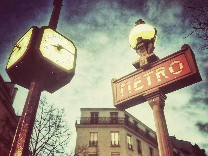 Paris Street Light Clocks At Street Clock Metro Metrostation France Paris Paris, France  Paris ❤ Paris Metro Sign Paris Metro Pole Post Sign Post City Text Road Sign Communication Sky Architecture Building Exterior Built Structure Information Information Sign Capital Letter Sign Written