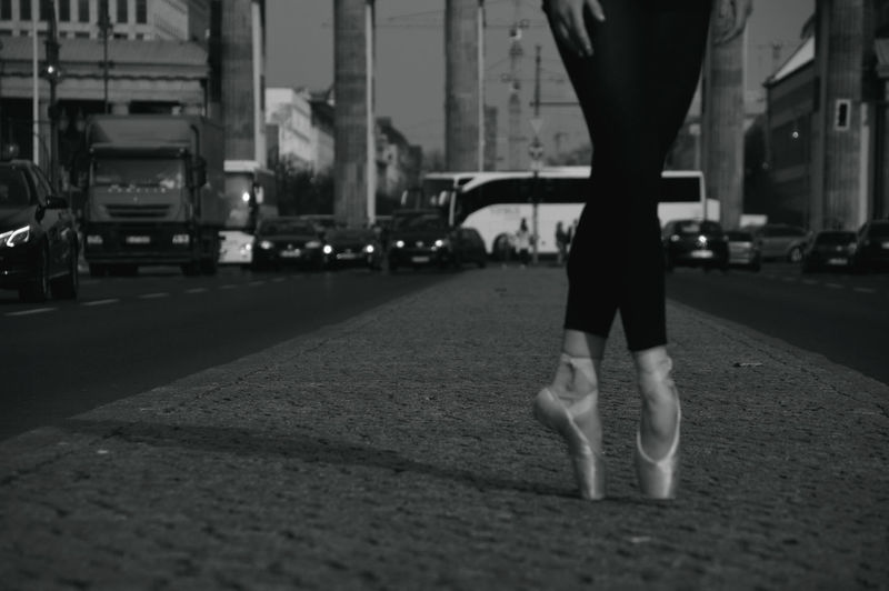 Low section of ballet dancer dancing on road in city
