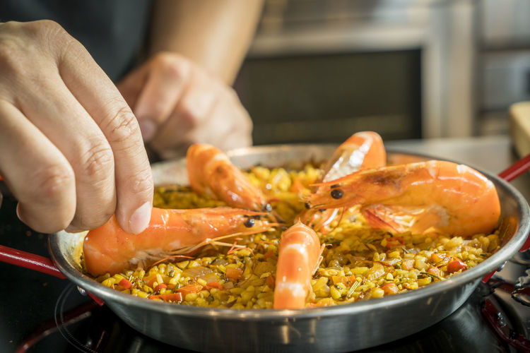 Cropped Image Of Chef Arranging Shrimp On Paella In Container