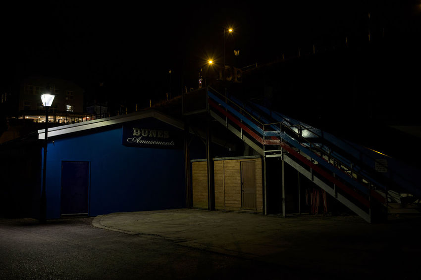 Late night in North Norfolk, United Kingdom. This image is of a blue building shrouded in darkness aside from the limited light from one lamp. Blue Built Structure Cromer Dark Deserted Late Night Nightphotography No People Norfolk Uk Outdoors Outside Outside Photography Shadow Street Lamp Travel Photography
