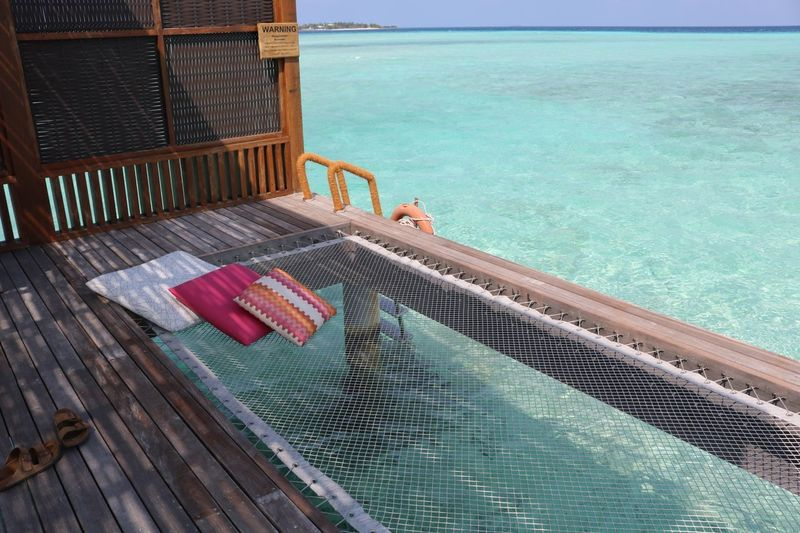 Photo of over-the-water bungalow's back porch Hammock Ocean Over Water Bungalow Bungalow On The Water Four Seasons Resort Maldives Islands Maldivesphotography Maldives Water Sea Day Nature High Angle View Railing No People Beach Tranquility Land Beauty In Nature Turquoise Colored Sunlight Tranquil Scene The Traveler - 2018 EyeEm Awards The Still Life Photographer - 2018 EyeEm Awards