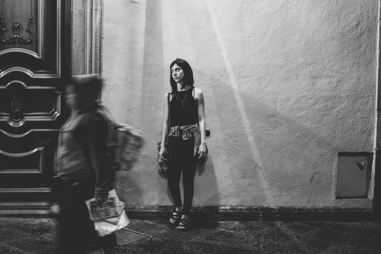 Woman Standing Against Wall In City At Night