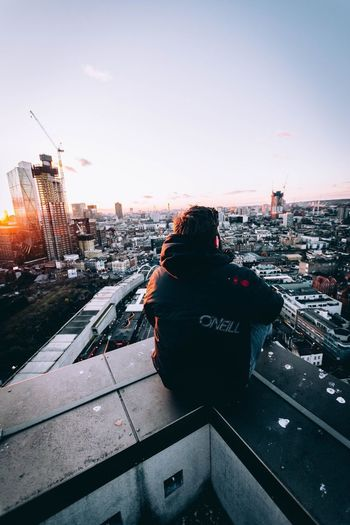 Rear view of man with cityscape against sky during sunset