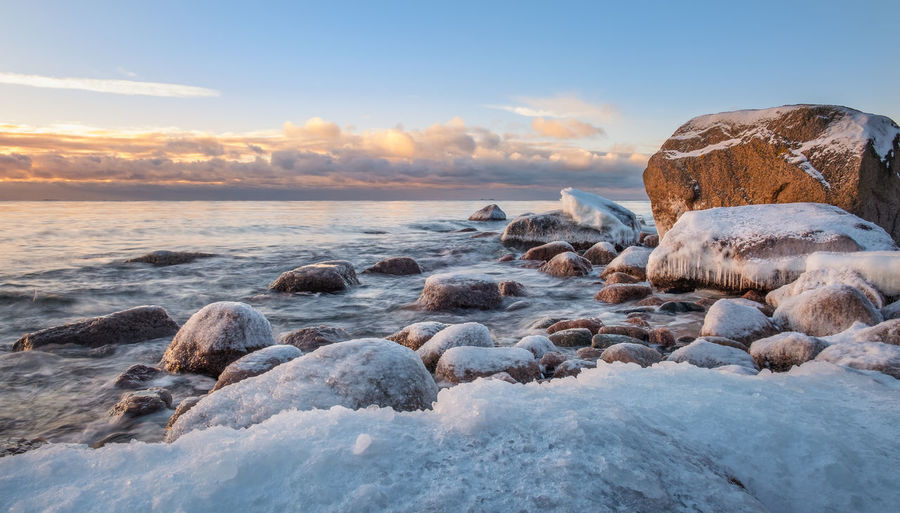 Scenic winter landscape with sea and sunrise at morning. Beautiful light with rocky coast in Finland. Sky Sea Water Rock Sunset Scenics - Nature Beauty In Nature Solid Rock - Object Nature Tranquil Scene No People Cloud - Sky Horizon Over Water Horizon Idyllic Finland Stone - Object Winter Landscape Sunrise Morning Light Evening Light Tranquility Peaceful Atmospheric Mood Nature Blue Snow Cold Temperature Frozen Frost Ice