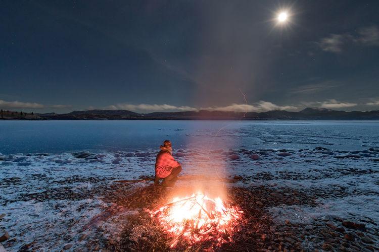 Man By Bonfire At Beach Against Sky