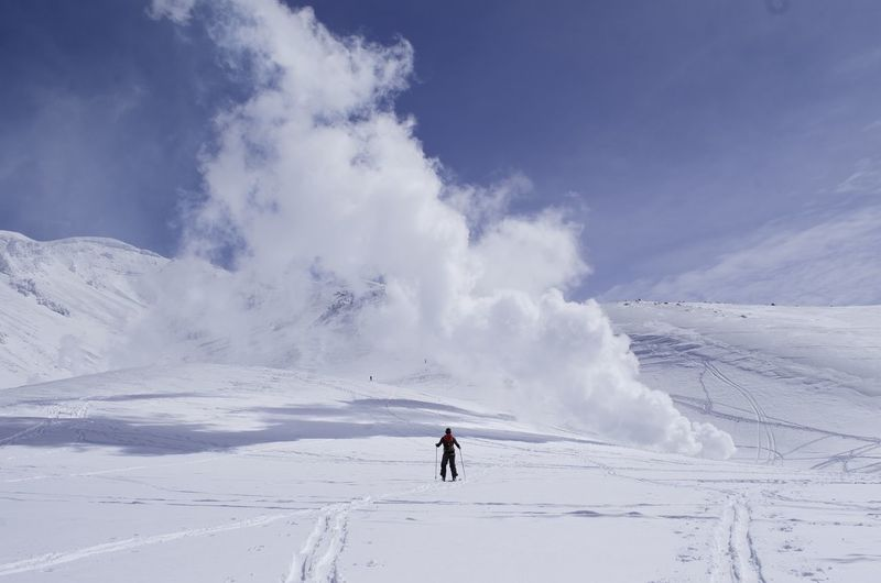 Rear View Of Person Skiing On Snowcapped Mountain Against Sky
