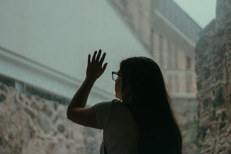 Rear view of woman touching wet window during rainy season