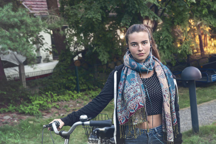 Portrait of woman with bicycle in park