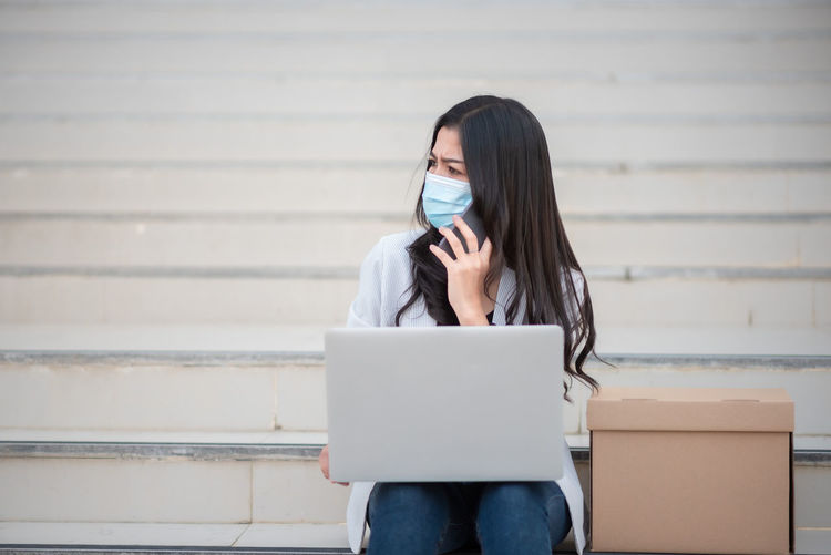 Businesswoman wearing mask while looking away outdoors
