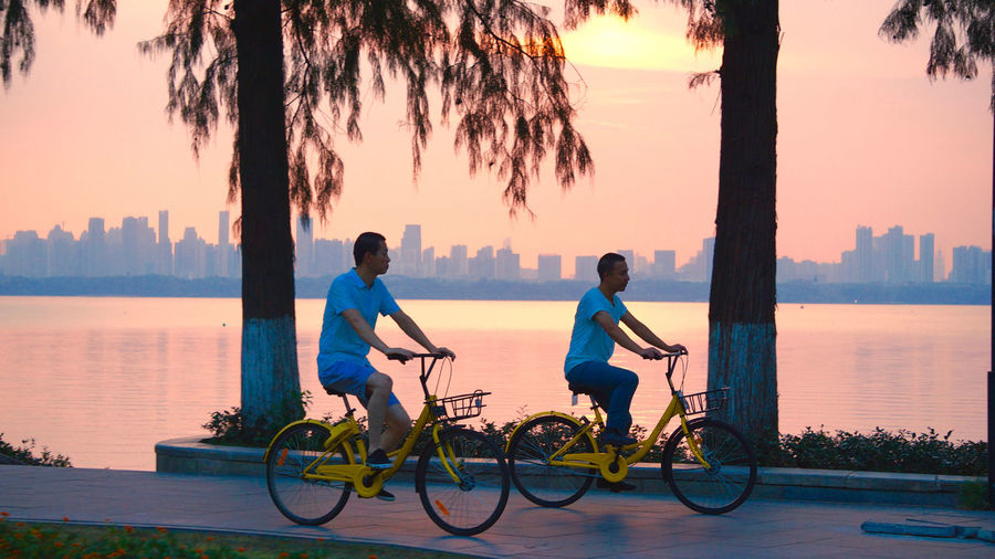 Men riding bicycle on water against sky