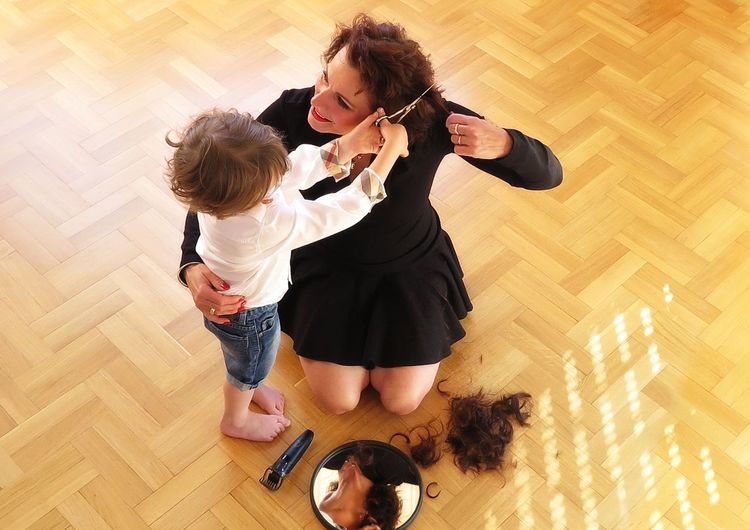 High angle view of woman and son on hardwood floor at home