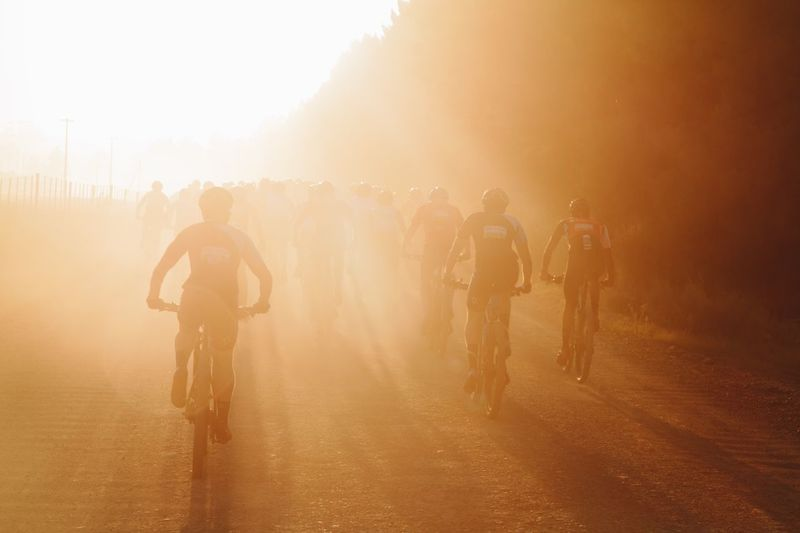 Cyclists against sky during sunset