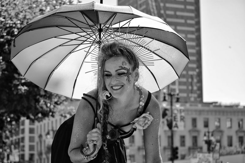 Young woman with umbrella standing in city