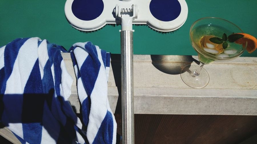 High angle view of brush with towel and drink on retaining wall against sea