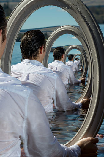 Multiple image of man with mirror in sea