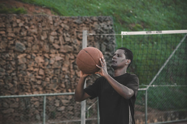 Young man playing basket ball at court
