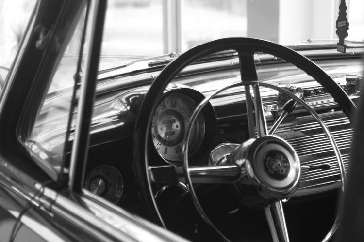 Close-up of steering wheel in vintage car seen through window