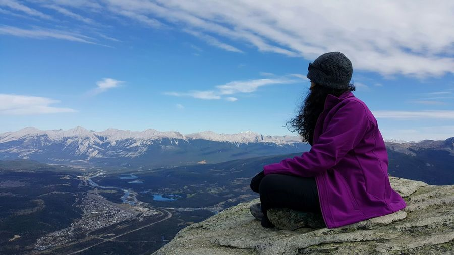 Woman sitting on top of mountain against sky