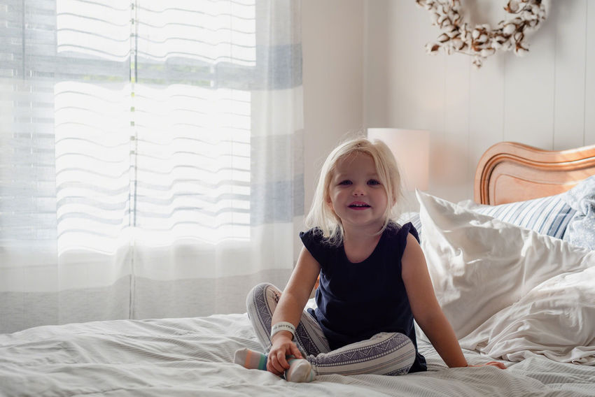 Little blonde girl on bed after waking up from nap Home Home Life Kids Nap Time Natural Light Relaxing Sitting Sunlight Bed Bedroom Blond Hair Child Childhood Comfortable Domestic Room Furniture Home Interior Indoors  Laying Down Laying In Bed Lifestyles Light And Bright Little Girl One Person Relaxation