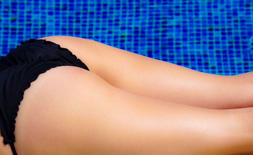 Close-Up Of Woman Relaxing By Swimming Pool