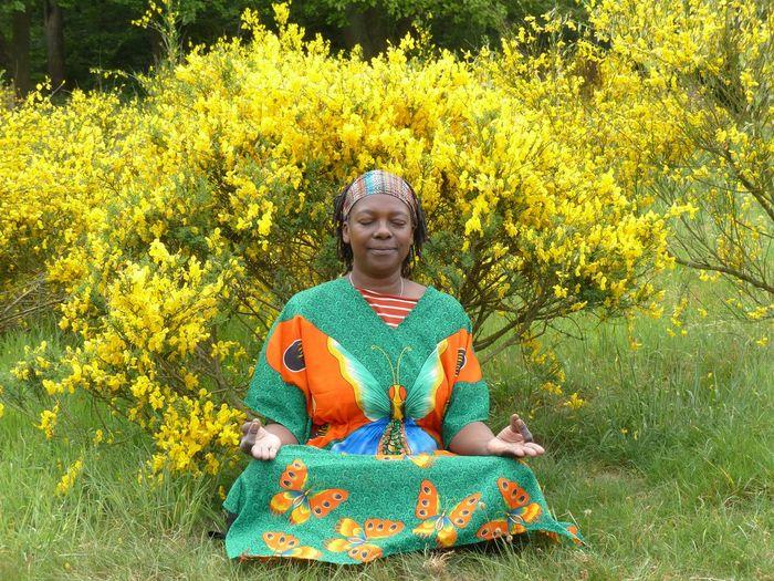 Mature Woman Meditating On Field Against Plants