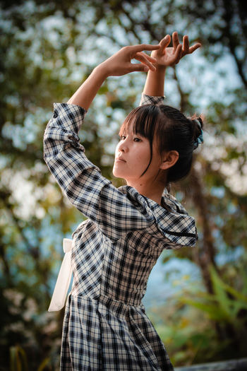 Low angle view of girl looking at tree