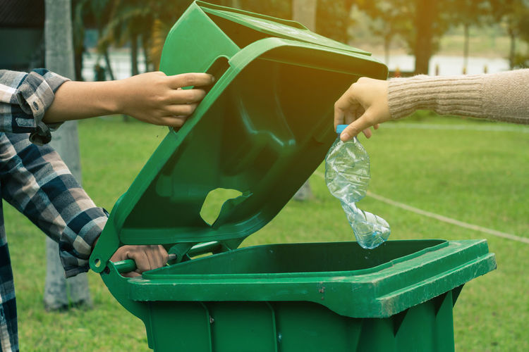 Hand holding dustbin