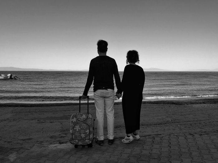 Couple with luggage standing at beach against