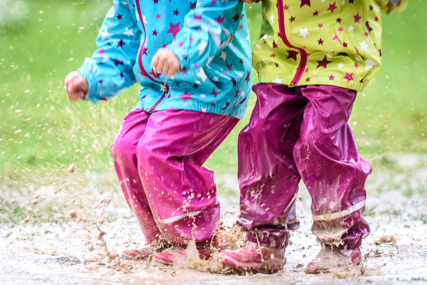 Children in rubber boots and rain clothes jumping in puddle. Water is splashing from girls feet as she is jumping and playing in the rain. Protective rubber pants and jacket for playing in the mud. Bad Weather Boots Children Pants Protection Clothing Puddles Rain Rainy Days Day Feet Game Jacket Jumping Legs Outdoors Outdoors Photograpghy  Outside Playing Puddle Rain Clothes Rain Jacket Rain Pants Rubber Boots Splashing Water