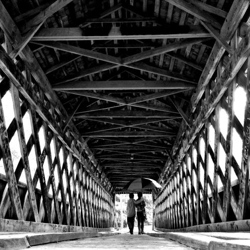 Rear view of couple walking on bridge