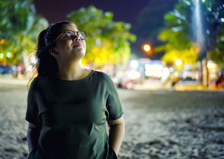 Mid adult woman swith hands in pockets standing on beach at night