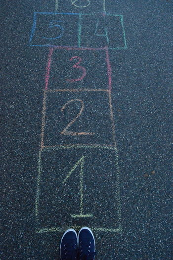 Low Section Of Person Standing Hopscotch On Footpath