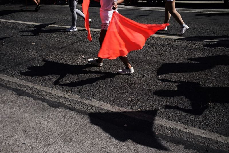 Low section of man with red flag walking on road