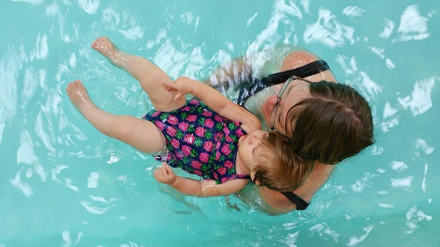 Directly above shot of mother carrying daughter in swimming pool
