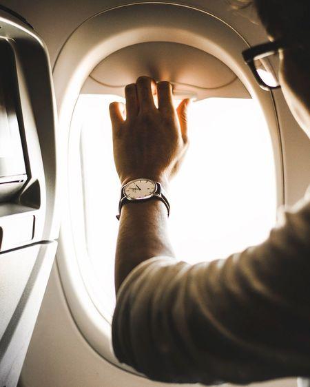 Close-up of man closing airplane window