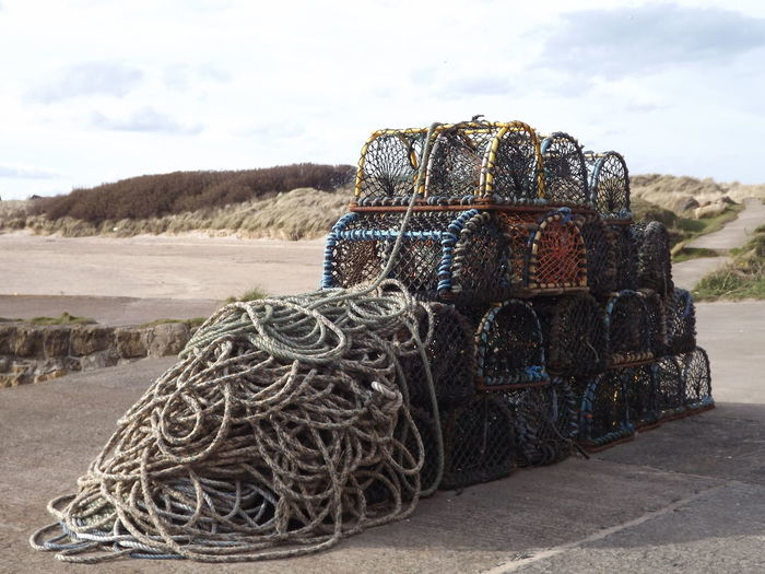 Stack Of Crab Pots And Ropes At Beach Against Sky