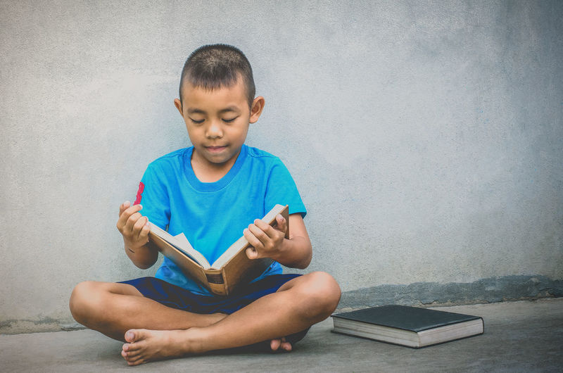 Boy studying against wall
