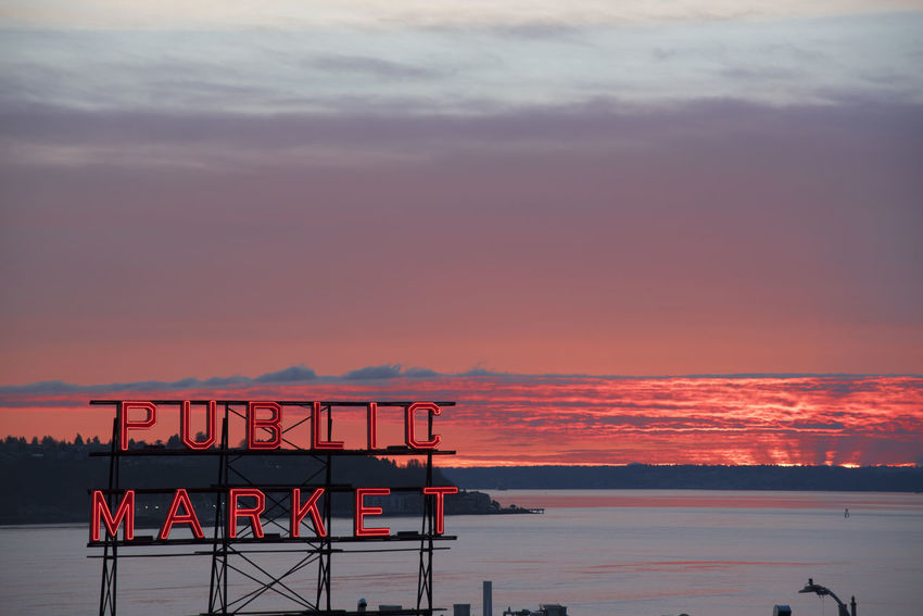 Pikes Place Market at sunset on the Seattle waterfront with neon Public market sign. Economy Elliott Bay Pink Post Alley Puget Sound Red Seattle Sign Tourists Travel View Washington Destination District Glowing Landmark Neon Pikes Place Market Public Market Shop Sky Sunset Tourism Vibrant