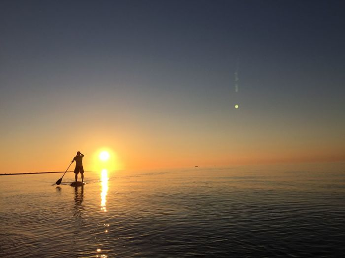 Silhouette Man Paddleboarding In Sea Against Clear Sky