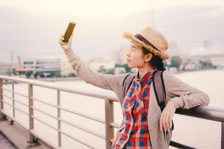 Smiling young woman taking selfie from mobile phone while standing on bridge