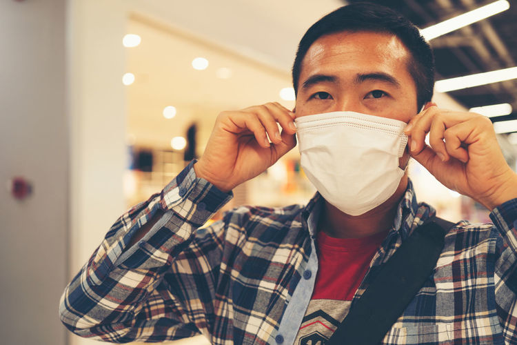 Portrait of man wearing mask in shopping mall